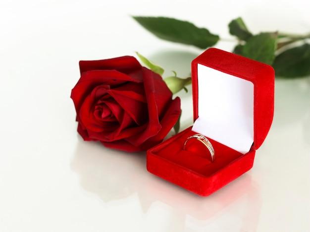 Une alliance dans une boîte rouge ouverte, à côté d'une rose écarlate.