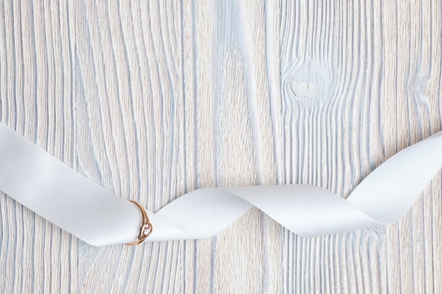Alliance en or avec un ruban sur un espace en bois. vue de dessus.