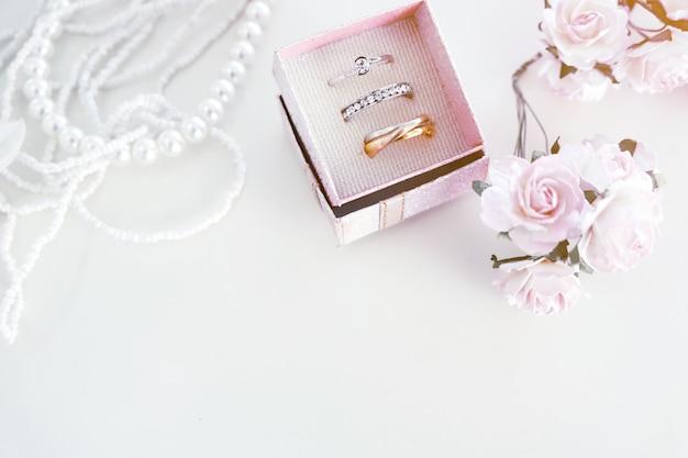 Alliances blanches dans des boîtes roses et roses pour les mariées