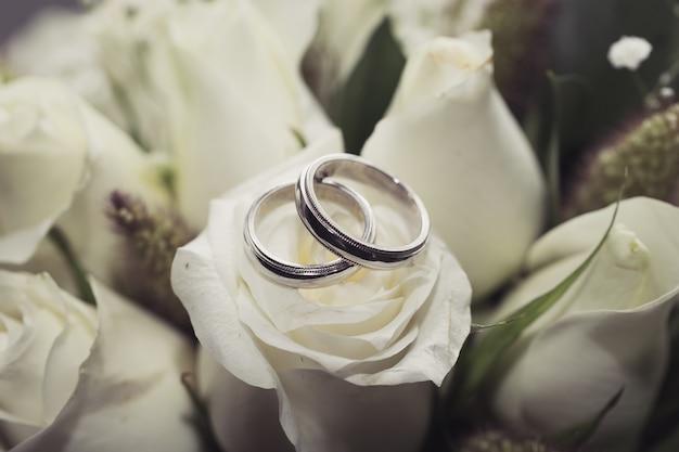 Alliances sur bouquet de roses blanches