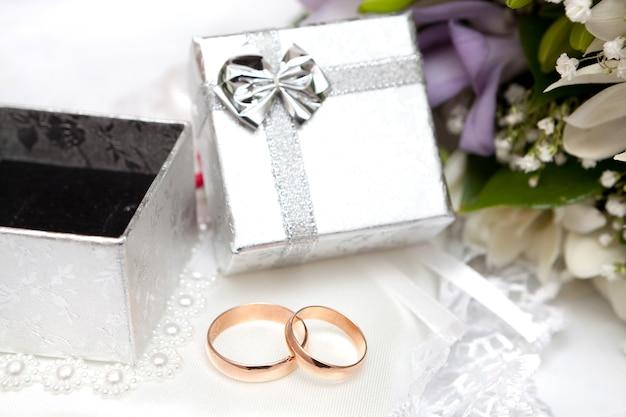 Alliances, coffret cadeau et fleurs pour la mariée.