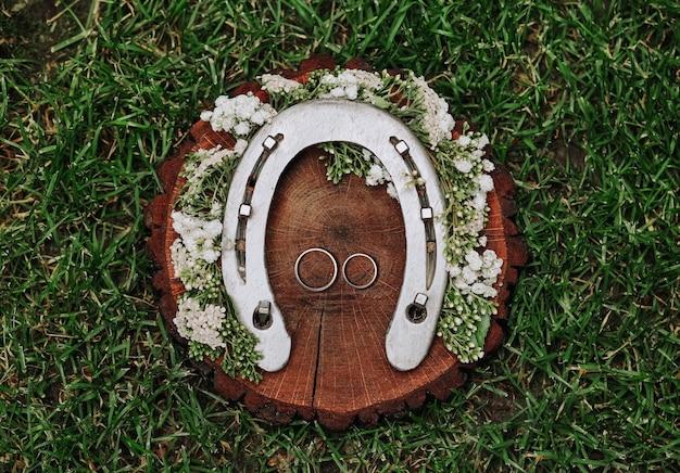 Alliances décorées sur une coupe en bois avec des fleurs blanches sur l'herbe