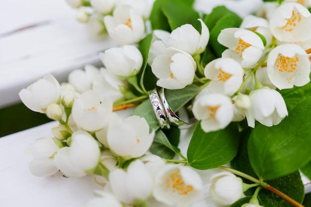 Des alliances dorées avec des diamants se trouvent à l'intérieur d'une fleur de jasmin (philadelphus) dans un bouquet de mariée