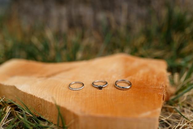 Alliances en or et bague de fiançailles sur une coupe en bois lisse sur l'herbe