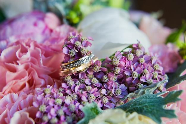 Alliances en or avec diamants sur le bouquet de la mariée.