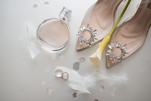 Alliances en or avec plumes à côté des chaussures beiges de la mariée décorées de pierres sur lesquelles se trouve une fleur jaune et à côté d'un flacon de parfum chanel