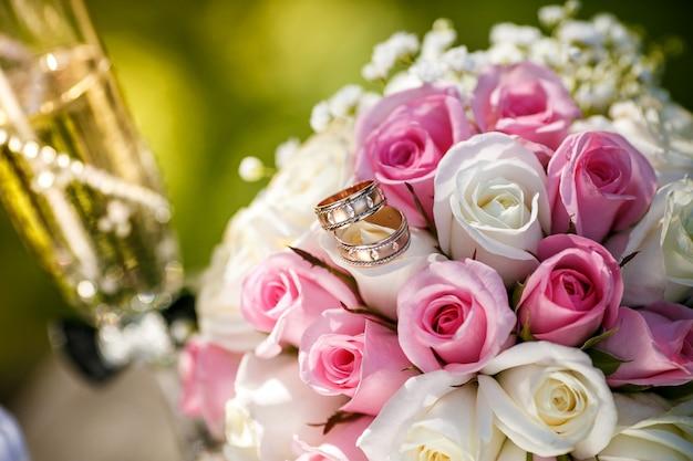Alliances or avec roses et coupes de champagne
