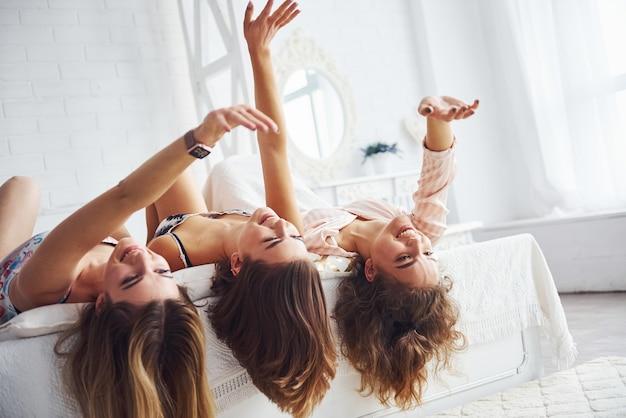 Allongé sur le lit avec les cheveux pendant. joyeuses amies s'amusant à une soirée pyjama dans la chambre.