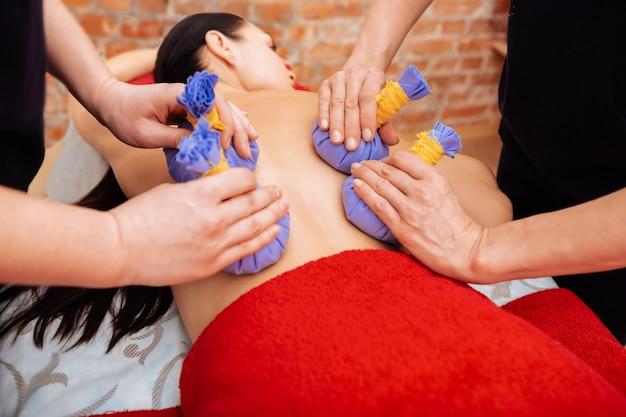 Allongé sur le ventre. femme partiellement nue recevant un traitement apaisant dans un salon et maîtres utilisant des sacs à base de plantes sur le dos