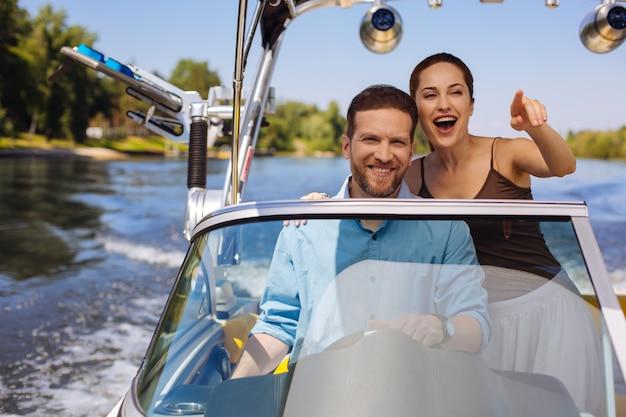 Allons-y. jeune femme optimiste montrant la destination souhaitable et pointant vers elle tout en naviguant sur un bateau avec son mari