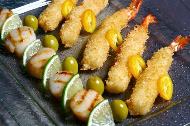 Allsorts de peignes de mer à la sauce à l'orange et aux crevettes tigrées crépitantes