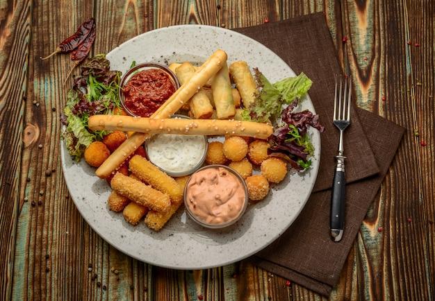 Allsorts de snacks frits avec deux sauces différentes sur fond noir