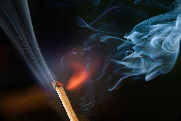 Allumage d'allumette avec de la fumée, isolé sur fond noir