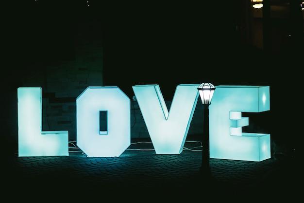 Allumée de grandes lettres bleues amour avec fond sombre