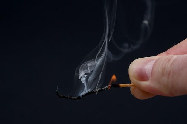 Allumette en bois brûlant et fumant dans la main sur l'obscurité