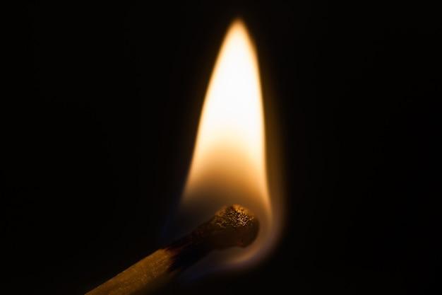 Allumette brûlante sur fond noir