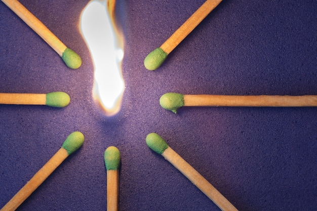 Allumette en feu sur le point de mettre le feu aux autres. mise à plat, vue de dessus.