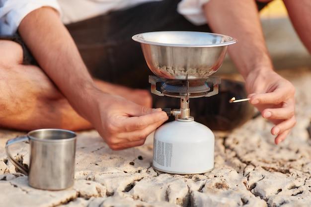 Allumette à la main masculine allumette à la cuisinière à gaz portable.