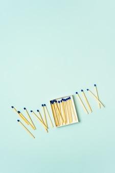 Allumettes en bois brillantes dispersées dans une boîte d'allumettes sur un fond de couleur pastel turquoise