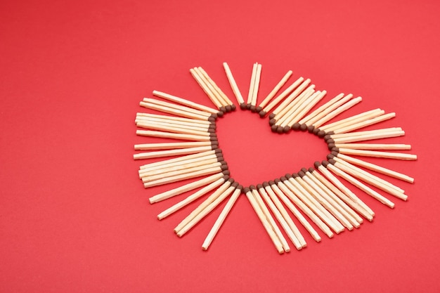 Allumettes en forme de coeur sur rouge