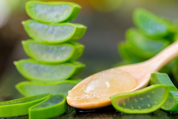 Aloe vera sur une cuillère en bois sur une table en bois il existe de nombreuses herbes utiles.