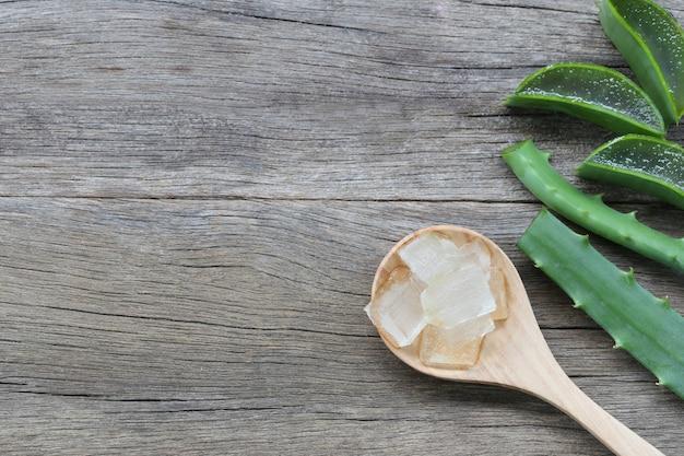 Aloe vera fraîche tranchée dans une cuillère en bois sur un plancher en bois marron.