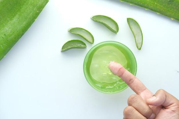 Aloe vera frais tranché et gel liquide dans un récipient en plastique sur une surface blanche