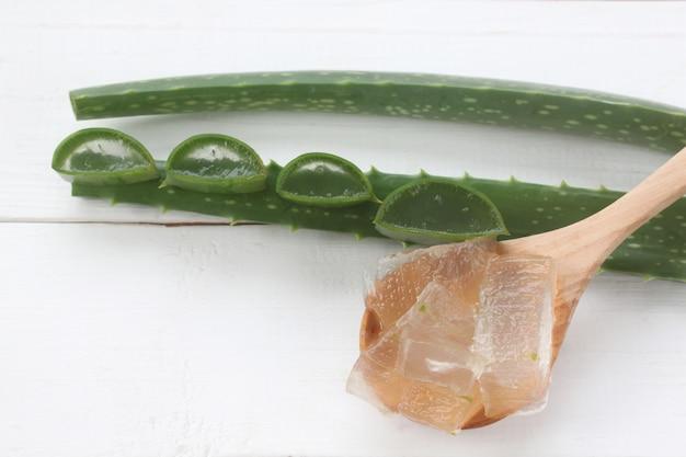 Aloe vera gel dans une cuillère en bois posée sur un bois blanc.