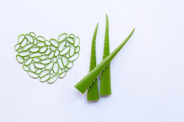 Aloe vera tranche en forme de cœur et aloe vera feuilles sur fond blanc.