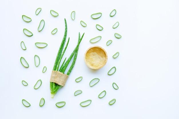 Aloe vera et tranches avec du gel d'aloe vera dans un bol en bois isolé on white