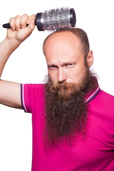 Alopécie humaine ou perte de cheveux - main d'homme adulte tenant un peigne sur une tête chauve.