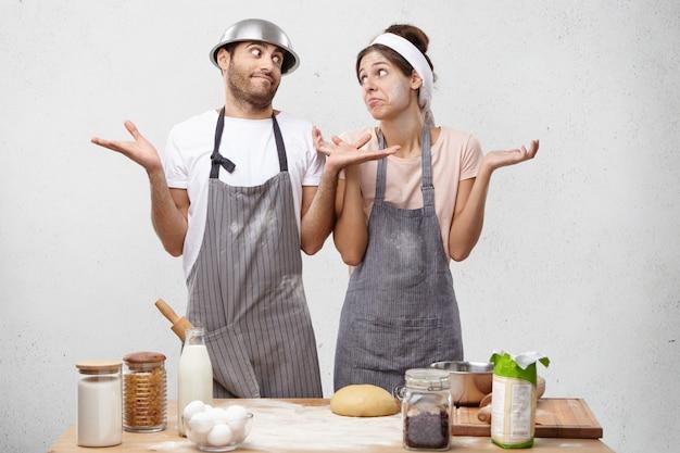Alors que faire? de jeunes cuisiniers désemparés haussent les épaules de stupéfaction,