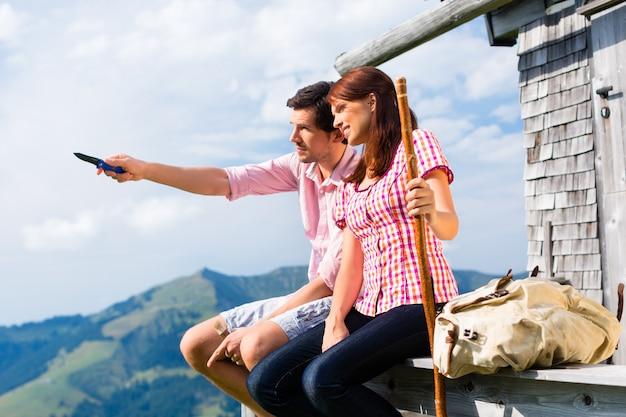 Alpes - homme et femme assis au chalet à tirol