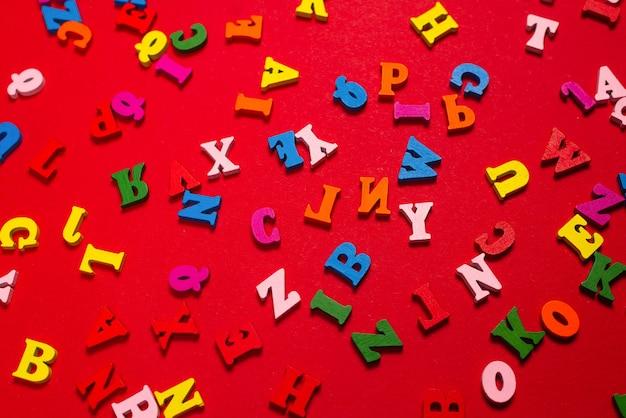 Alphabet coloré aléatoire sur fond rouge, lettres colorées. vue de dessus.