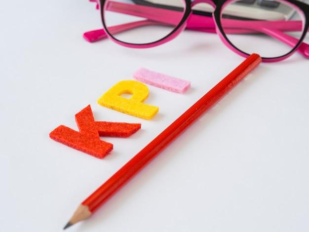 Alphabet kpi avec un crayon rouge et des lunettes roses sur fond de tableau blanc.