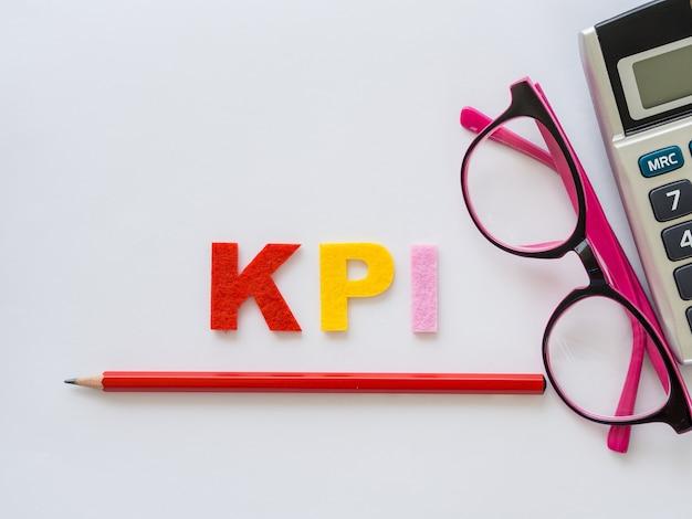 Alphabet kpi avec un crayon rouge et des lunettes roses mis sur fond de table blanche.