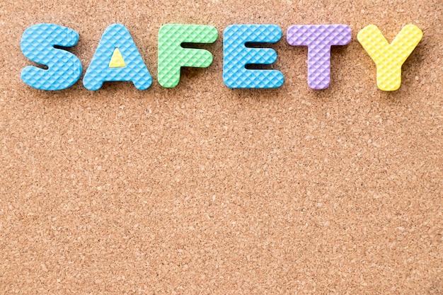 Alphabet de mousse de jouet de couleur dans le mot sécurité sur fond de panneau de liège