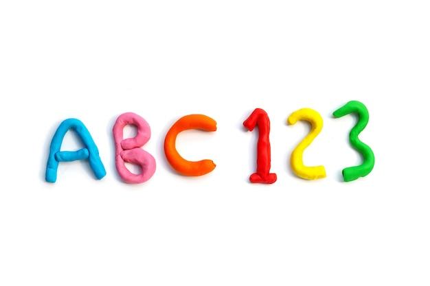 Alphabet avec numéro en pâte à modeler colorée sur blanc.