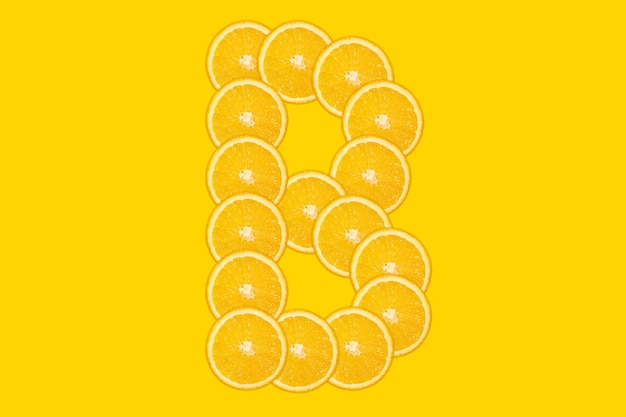 Alphabet orange en tranches - lettre b. fond jaune. fruit orange frais et sain. police juteuse.
