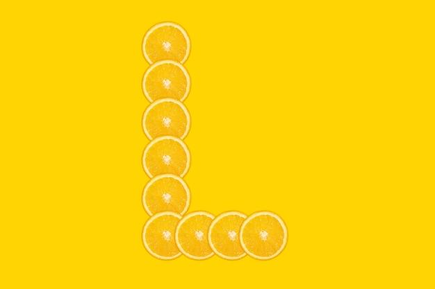 Alphabet orange en tranches - lettre l. fond jaune. fruit orange frais et sain. police juteuse.