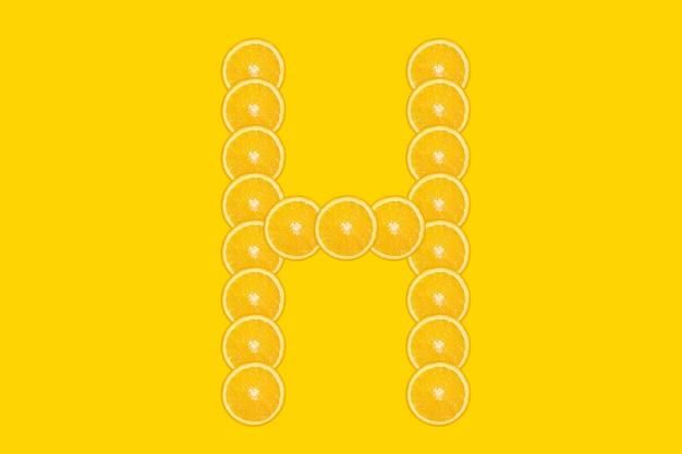 Alphabet orange en tranches - lettre h. fond jaune. fruit orange frais et sain. police juteuse.