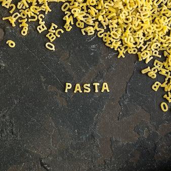 Alphabet de pâtes et ingrédient pour sauce (ensemble d'ingrédients, pâtes crues) servant un deuxième plat. fond de nourriture haut. espace de copie