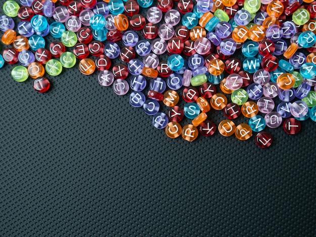 L'alphabet perle multi couleur sur fond noir pour le concept de l'éducation