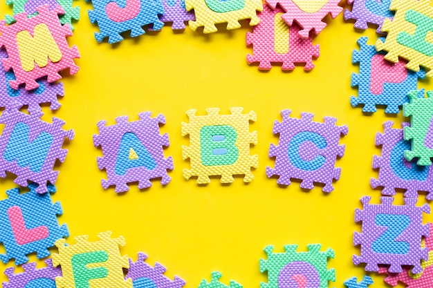 Alphabet puzzle sur jaune.
