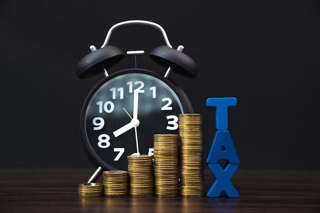 Alphabet tax avec pile de pièces de monnaie et réveil vintage