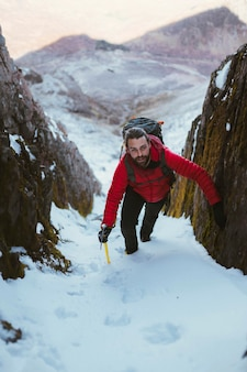 Alpiniste escaladant une montagne de neige