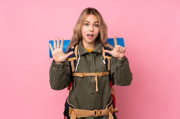 Alpiniste russe adolescent fille avec un gros sac à dos isolé sur mur rose comptant sept avec les doigts