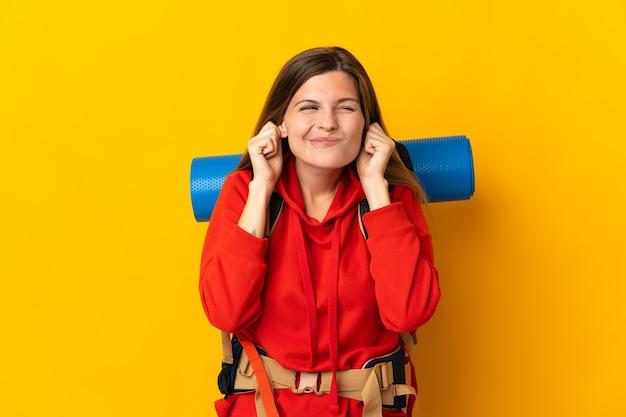 Alpiniste slovaque femme avec un gros sac à dos isolé sur mur jaune frustré et couvrant les oreilles
