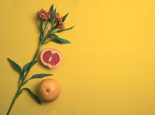 Alstroemeria et pamplemousse sur fond jaune. vue de dessus