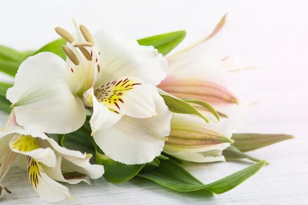 Alstromeria des fleurs dans la boîte en bois, bougie allumée